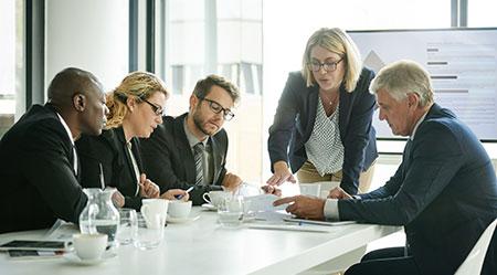Réunion en présentiel avec une femme présentant une feuille de route pragmatique à un Comex ou comité exécutif de quatre personnes d'une entreprise